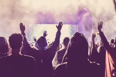 Crowd of audience with hands raised at a music festival. Lights streaming down from above the stage Royalty Free Stock Images