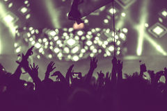 Crowd of audience with hands raised at a music festival. Lights streaming down from above the stage Stock Images