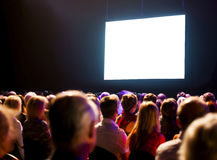 Crowd audience looking at screen. Crowd audience in dark looking at bright screen Royalty Free Stock Photography