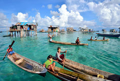 Crowd of Bajau Laut people paddles a boats. SABAH, MALAYSIA - APR 19: Crowd of Bajau Laut people paddles a boats in Bodgaya Island on April 19, 2015. They are Royalty Free Stock Images