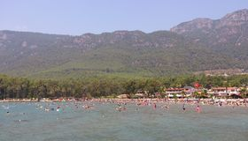 Crowd at the beach in Akyaka, Turkey. Many people at the beach in seaside of Akyaka, Turkey with forest and mountain on background Stock Photos