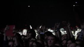 Crowd in big concert in front of bright stage lights stock video footage