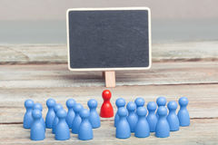 Crowd of blue pawns, with red pawn and copy space blackboard Royalty Free Stock Image