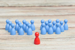 Crowd of blue pawns, with red pawn Stock Photos