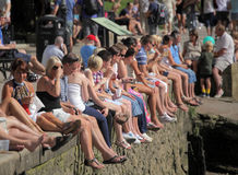 Crowd catching the sun. Crowd of people sitting on a wall on the bank of river Thames in Richmond, London, on a very hot summer day Royalty Free Stock Photos
