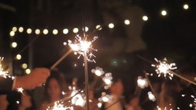 Crowd celebrate at dark evening. Festival fire firework. Friends have fun in group. Slow motion. Happy people are holding burning Bengal lights in wedding night stock video footage