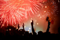 Crowd celebrating the New Year with fireworks Stock Photo
