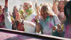A crowd of children decorated with paint having fun in front of the stage. Close up. stock footage