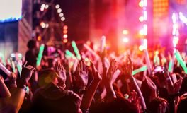 Crowd clap or hands up at concert stage lights. And people fan audience raising hands silhouette with spotlights glowing effect in the music festival rear view royalty free stock images