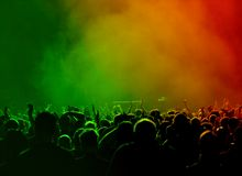 Crowd at concert. People raising hands in front of a stage at a concert - cheering crowd and a lot of heads and hands in the air Royalty Free Stock Image