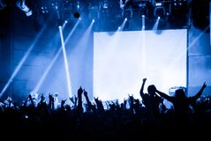 Crowd at concert on the background of stage with a blank white screen. Cheering crowd at concert on the background of stage with a blank white screen Stock Photo