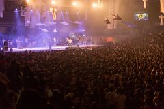 Crowd at concert and blurred stage lights, noise added later in. Post processing for vintage usage royalty free stock images
