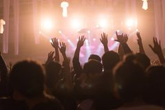 Crowd at concert and blurred stage lights, noise added later in. Post processing for vintage usage royalty free stock image