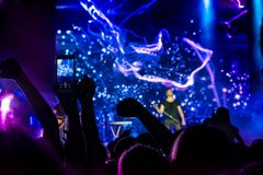 Crowd at concert. People silhouettes on backlit by bright blue and purple stage lights. Cheering crowd in colorful stage lights. R. Aised hands and smartphones royalty free stock images