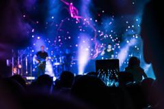 Crowd at concert. People silhouettes on backlit by bright blue and purple stage lights. Cheering crowd in colorful stage lights. R royalty free stock photo
