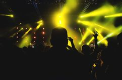 Crowd at concert - silhouettes of concert crowd in front of bright stage lights. Crowd at concert - silhouettes of concert crowd in front of bright stage yellow royalty free stock photography
