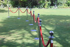 Crowd control barriers with red velvet rope. Steel barrier security posts with red velvet rope separating two areas of a garden for a function or party Stock Images