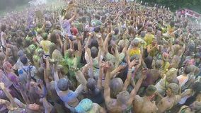 Crowd covered in colored powder paint, festival atmosphere. Stock footage stock video footage