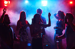 Crowd dancing in night club. Silhouettes of young dressed-up people dancing in club smoke with glasses of champagne Stock Image