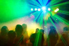Crowd dancing under disco laser beam. Festive atmosphere of people dancing under disco laser beam Stock Image