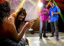 Crowd Enjoying Drinks at Nightclub. Mixed crowd drinking and socializing in a nightclub Stock Photo