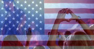 Crowd enjoying time at concert with American flag. Digital composite of woman enjoying Concert with hands forming heart against american flag background stock video footage