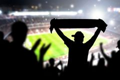 Crowd and fans in football stadium. People in soccer game. Person celebrating goal and holding merchandise scarf for favourite club and team in match. Happy Royalty Free Stock Photo