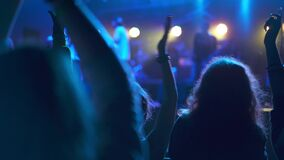 Crowd of fans of the musical band applauding in a nightclub during live performance. Rock concerts where people dancing