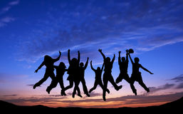 Crowd of friends jumping on blue sky background Stock Images