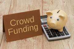 Crowd Funding, A golden piggy bank, card and calculator on wood Royalty Free Stock Images