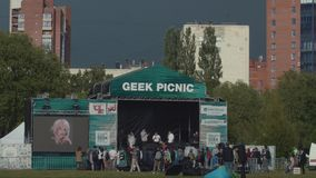 Crowd gather near scene with stand up performance at city park summer festival. Sunny day with big dark rainy cloud on horizon stock video footage