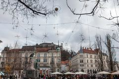Crowd gathered for Christmas market on Presernov Square with Tromostovje bridge and Ljubljana castle in the background. NPicture of Presernov square in stock images