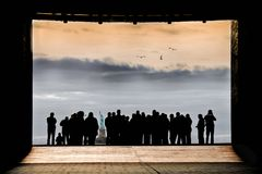 CROWD IN SILHOUETTE TOGETHER LOOKING AT STATUE OF LIBERTY NEW YORK. Crowd gathered in silhouette with gap showing Statue of Liberty in New York City looking at stock photography