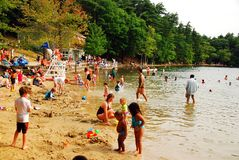 Summer at the pond. A crowd gathers on a busy summer`s Day at Walden Pond, Massachusetts Stock Photography