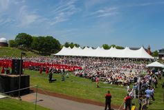 Crowd and graduates sit in front of tent at outdoor Wesleyan University Graduation Middletown Conneticut USA circa May 2015. A Crowd and graduates sit in front Stock Photos
