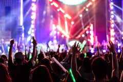Crowd of hands up concert stage lights. And people fan audience silhouette raising hands in the music festival rear view with spotlight glowing effect royalty free stock photography