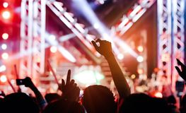 Crowd of hands up concert stage lights. And people fan audience silhouette raising hands or glow stick holding in the music festival rear view with spotlight royalty free stock photography