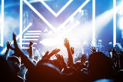 Crowd of hands up concert stage lights. And people fan audience silhouette raising hands in the music festival rear view with spotlight glowing effect stock images