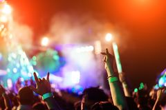 Crowd of hands up lovers concert stage lights. And people fan audience silhouette raising hands in the music festival rear view with spotlight glowing effect royalty free stock photography