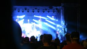Crowd has fun at metal concert event show shake head silhouette fan long hair stock footage