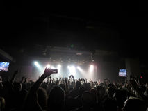 Crowd hold hands and cellphone in air as lights overwhelm stage Stock Photo