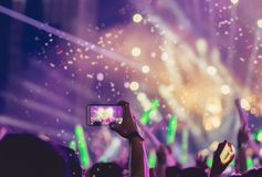 Crowd holding smartphone at concert stage. Lights and people fan audience silhouette raising hands in the music festival rear view with spotlight glowing effect royalty free stock photo