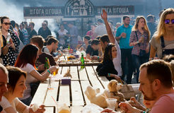 Crowd of hungry people eating meals around tables outdoor during Street Food Festival Stock Photos