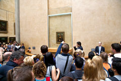 Crowd at louvre. Young tourists look at a well-protected Mona Lisa (by Leonardo da Vinci) at the Musée du Louvre, Paris, France.i Royalty Free Stock Images