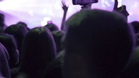 Crowd making party at rock concert and hands hold many cameras with digital displays among people. Hands hold many cameras with digital displays among people stock footage