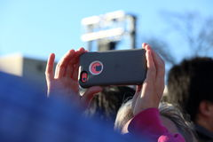 Crowd member takes photo with Apple Iphone at political rally. A member of the crowd holds her iphone over her head to take a picture of the speaker at a rally royalty free stock photography