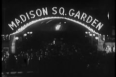 Crowd milling beneath neon Madison Square Garden marquee, 1930s stock video footage