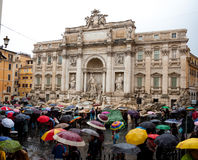 Crowd with multi color umbrellas is standing near Trevi fountain.
