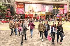 Crowd of multiracial people crossing Nathan Road in Hong Kong Stock Images