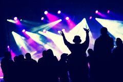 Crowd at a music concert, audience raising hands up Stock Photo